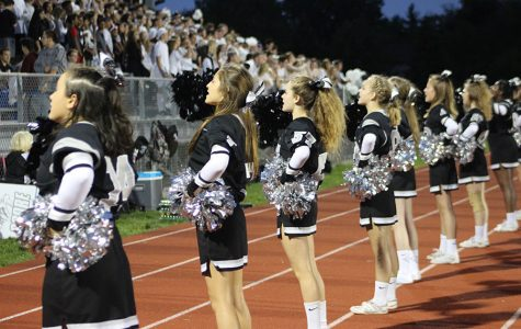 The cheerleaders in front of the student section help keep up the school spirit as Churchill gets ahead during Plymouth's Homecoming game.