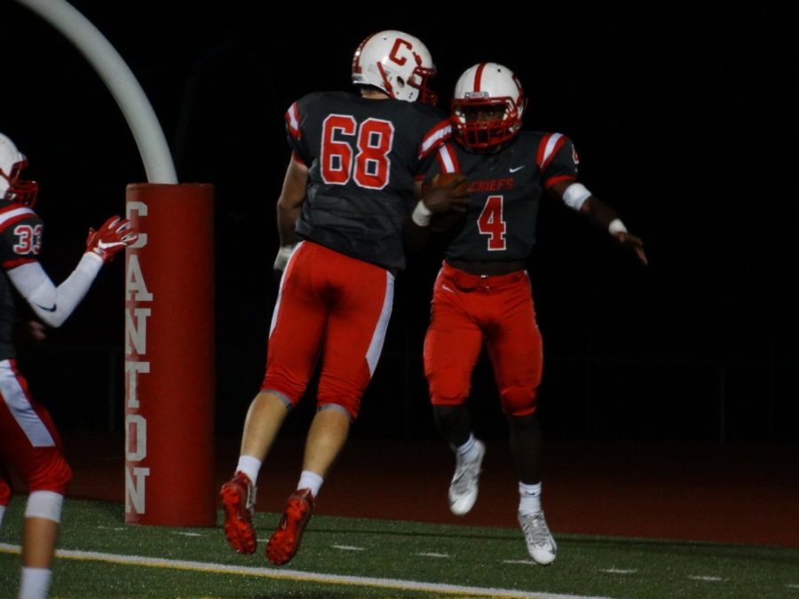 Players John Valchine (left) and Steven Walker (right) celebrate Walker's third touchdown in the game.