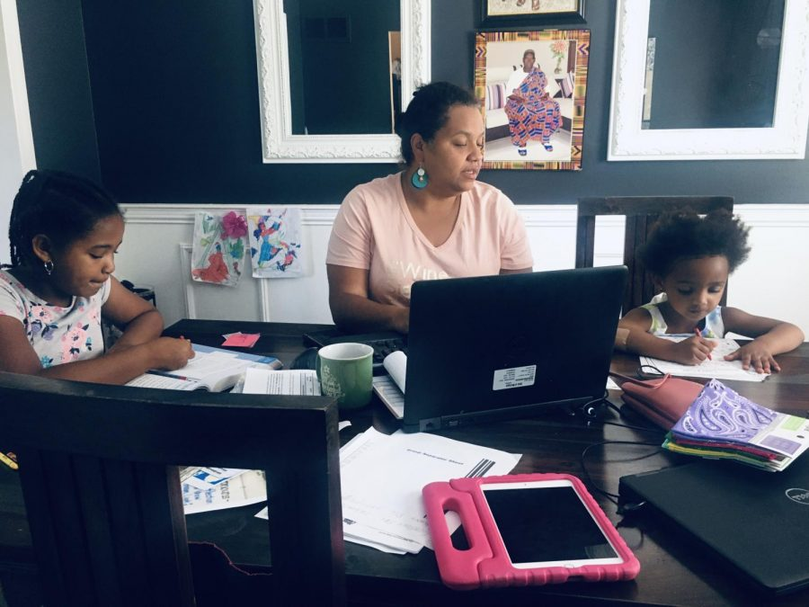 Nicole Denson-Sogbaka helps her kids with their assignments as she works from home.